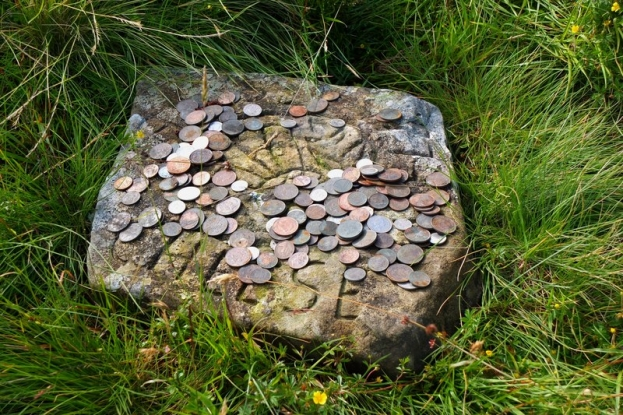 Why do walkers leave coins at Cheese Well?
